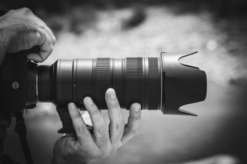 Hands holding a digital SLR camera with zoom digital lens - slon.pics - free stock photos and illustrations