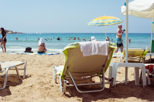 Sunbed on the beach with unrecognizable people on background - slon.pics - free stock photos and illustrations