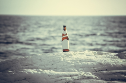Bottle of beer with blank label on the beach - slon.pics - free stock photos and illustrations
