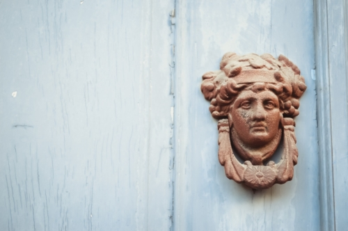 Decorated face door knob made of metal on a blue wooden door - slon.pics - free stock photos and illustrations