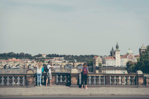 Travelers with backpacks taking photos of Prague at Legion Bridge (Most Legii) - slon.pics - free stock photos and illustrations