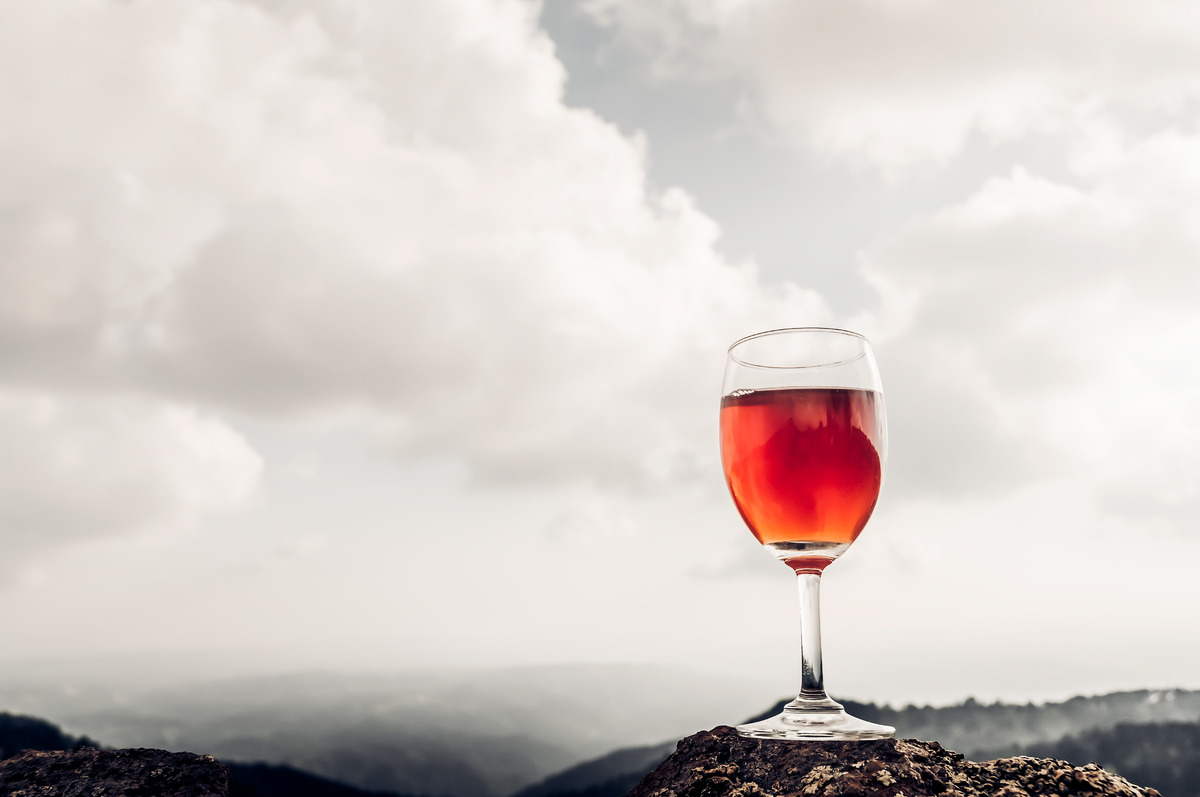 A glass of rose wine in front of a mountainous landscape - slon.pics - free stock photos and illustrations