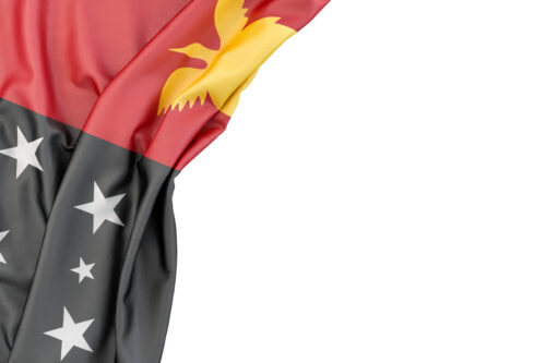 Flag of Papua New Guinea in the corner on white background. Isolated, contains clipping path - slon.pics - free stock photos and illustrations