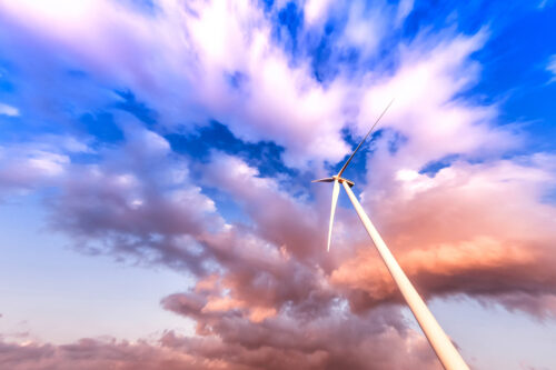 Wind turbine in action against a cloudy blue sky - slon.pics - free stock photos and illustrations