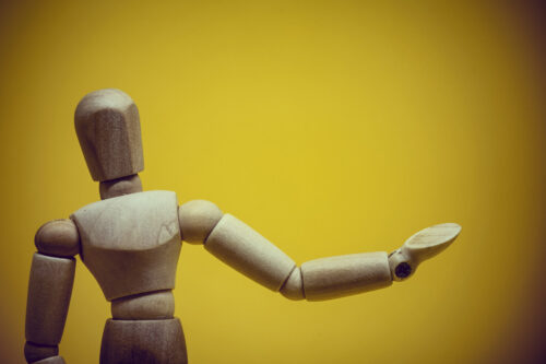 Wooden mannequin presenting invisible object - slon.pics - free stock photos and illustrations