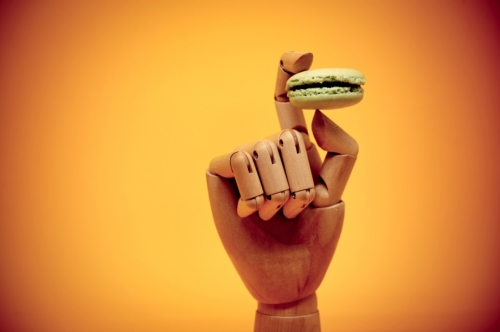 Wooden hand holding macaroon - slon.pics - free stock photos and illustrations
