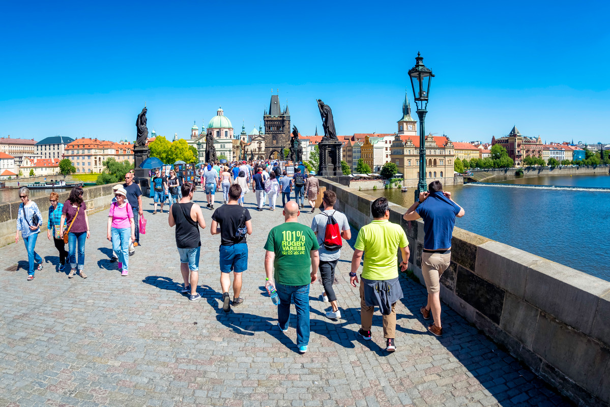 Tourists walking along the Charles Bridge while sightseeing in Prague. Czech Republic - slon.pics - free stock photos and illustrations