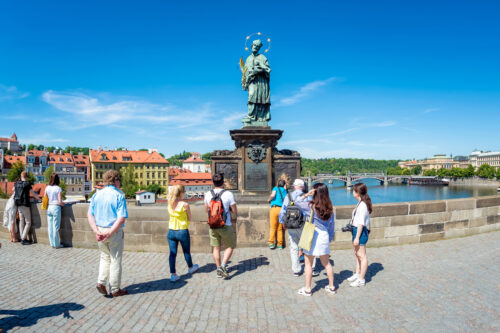 Tourists touching a bronze plaque for luck on the St John of Nepomuk statue at Charles bridge. Prague, Czech Republic. - slon.pics - free stock photos and illustrations