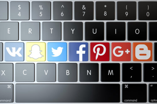 Various social networks and services icons on laptop keyboard. Technology concept - slon.pics - free stock photos and illustrations