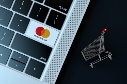 Mastercard logo on laptop keyboard and miniature shopping cart - slon.pics - free stock photos and illustrations