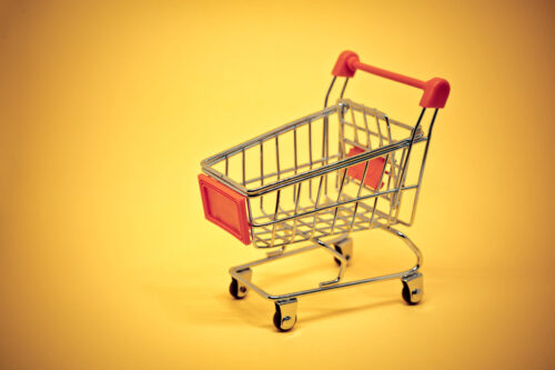 Miniature shopping cart on yellow background - slon.pics - free stock photos and illustrations