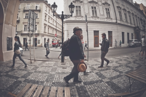 Man with backpack walking on a town center pavement street. Czech Republic. May 25, 2017 - slon.pics - free stock photos and illustrations