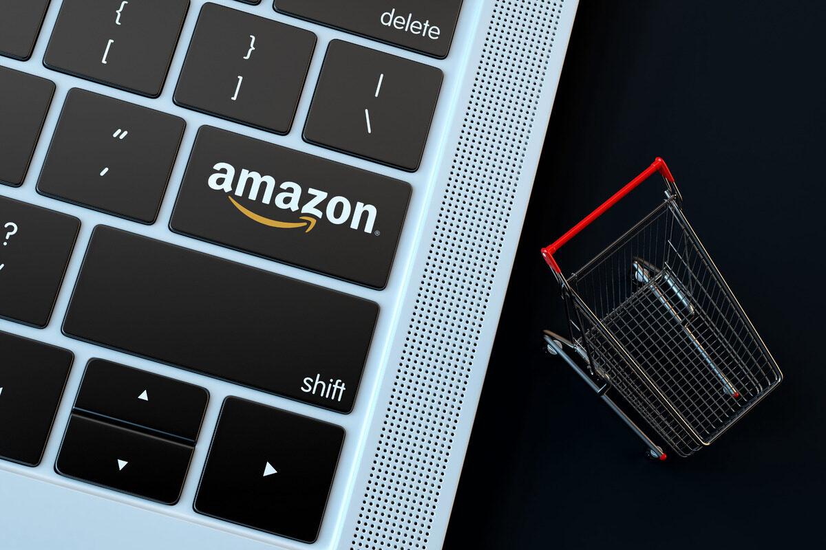 AMAZON logo on laptop keyboard and miniature shopping cart - slon.pics - free stock photos and illustrations