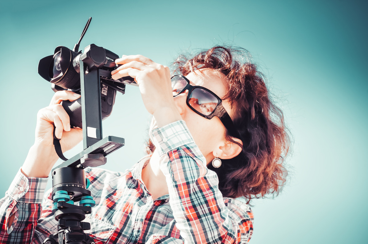 Woman mounting camera on a tripod - slon.pics - free stock photos and illustrations