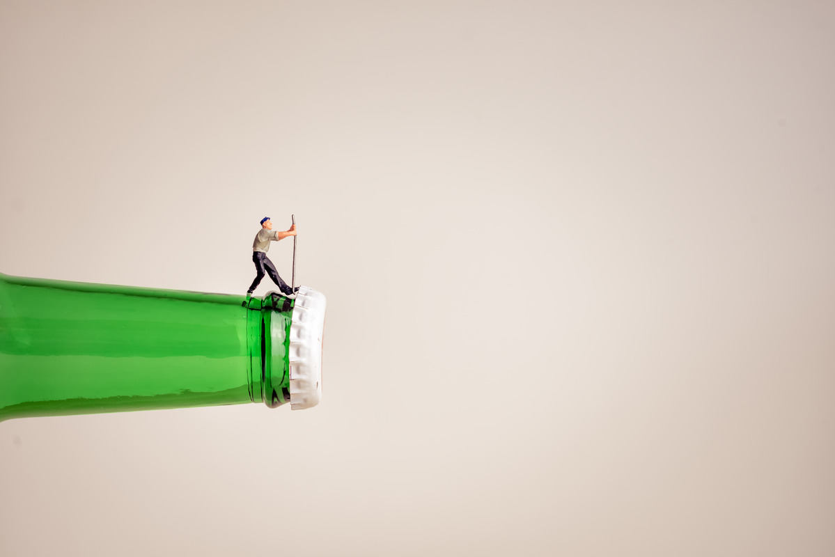 Closeup of a miniature worker opening a bottle - slon.pics - free stock photos and illustrations