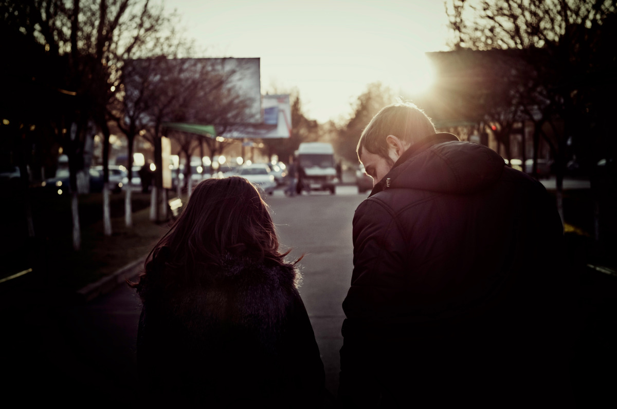 Rear view of young couple holding walking through the city street - slon.pics - free stock photos and illustrations