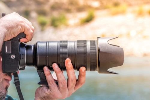 Side view of a photographer holding camera - slon.pics - free stock photos and illustrations