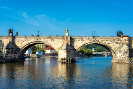 Charles Bridge over Vltava River against blue sky. Prague, Czech Republic - slon.pics - free stock photos and illustrations