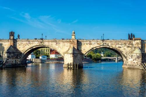 Charles Bridge over Vltava River against blue sky. Prague, Czech Republic - slon.pics - free stock photos and illustrations